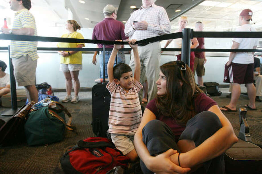 Ready for a flight to Miami, Lupita McWilliams and her son, Devin, wait in boarding group A at Hobby Airport on Wednesday. Photo: MAYRA BELTRÁN, Chronicle
