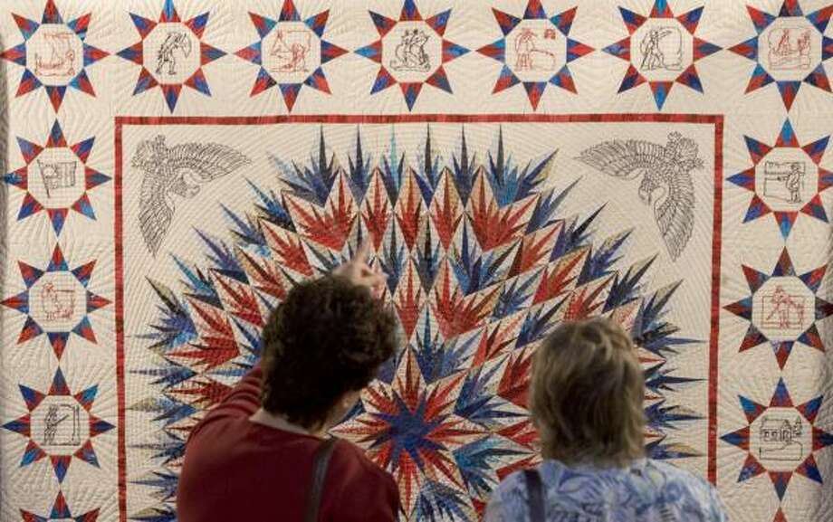 Valli Schiller, left, and Stephanie Nordlin pause to take a look at one of the quilts on display during a special winners' preview at the International Quilt Festival at the George R. Brown Convention Center. Photo: BRETT COOMER, CHRONICLE