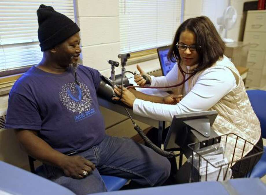 David Thomas gets his blood pressure checked by nurse Brenda Buchanan at a clinic that works with the New Like Presbyterian Church Food Pantry in Milwaukee. Photo: DARREN HAUCK, ASSOCIATED PRESS