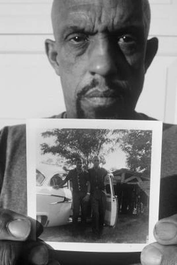 In 2005, Thomas Moore holds a photo of himself, right, and his younger brother, Charles, who was kidnapped and killed in 1964 in Mississippi. Photo: David Ridgen, AP