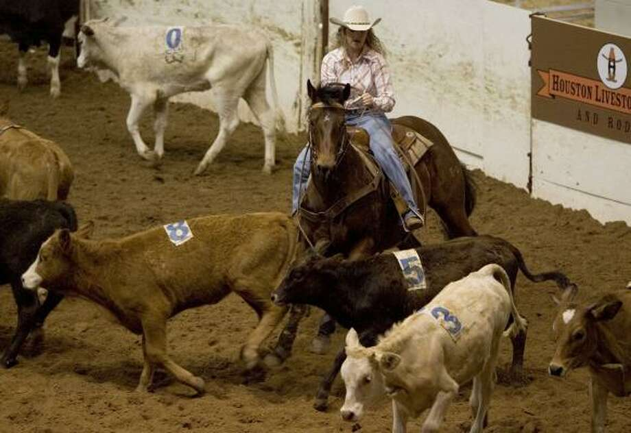 Candace Teague, of Tahlequah, Okla., works to separate a calf from a herd of 30 as she competes in team penning on Tuesday in Reliant Arena. Photo: BRETT COOMER, CHRONICLE