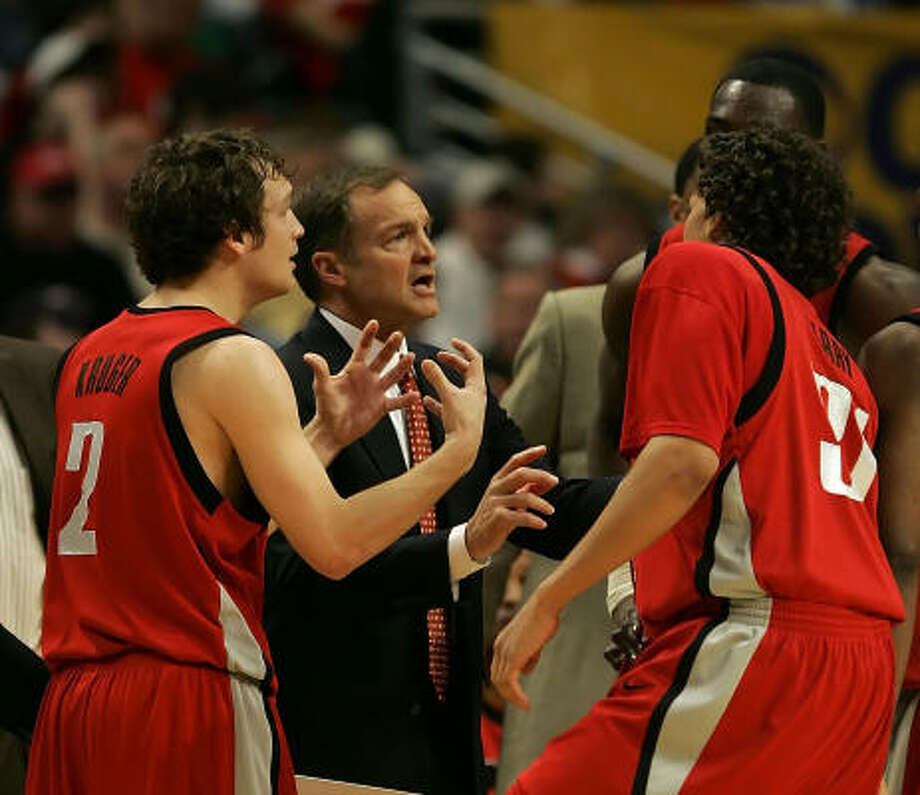 UNLV coach Lon Kruger, center, talks to his players, including his son Kevin, left, during a timeout late in Sunday's game. The younger Kruger hit three 3-pointers late in the game to help the Runnin' Rebels knock off second-seeded Wisconsin 74-68 and advance to the Midwest Regional semifinals. Photo: Jonathan Daniel, Getty Images