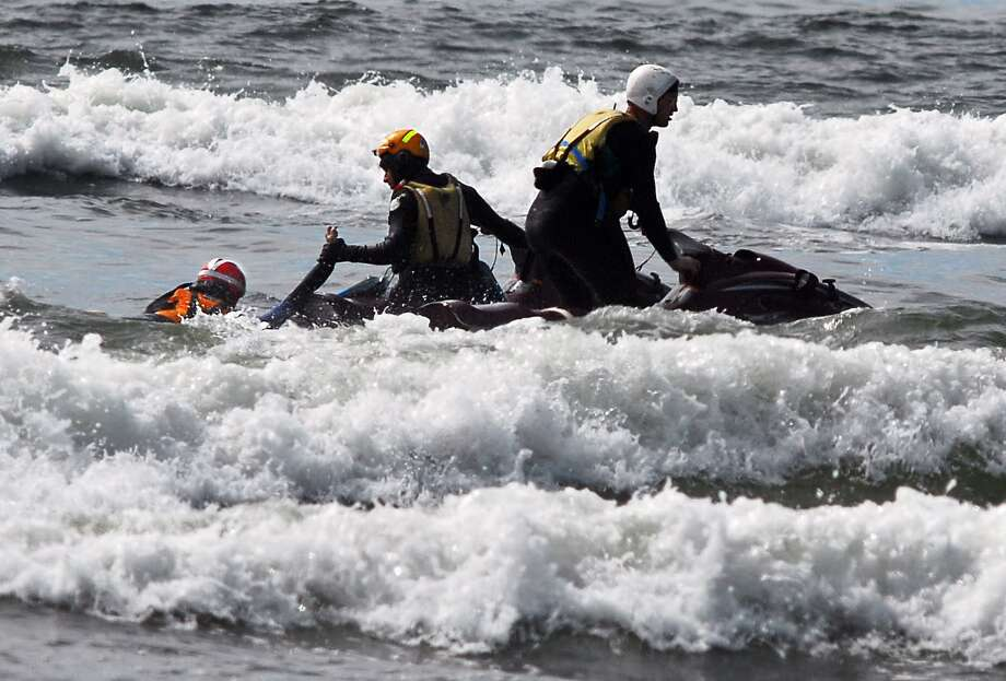 Surf rescue swimmers Eddie  Mendez and Will Green pull  Dale Ostrander aboard their jet ski after  finding him in the surf off the Cranberry Road beach approach near Long  Beach on Friday,. The team searched for the boy for  nearly 15 minutes before finding him.  (AP Photo/Damian Mulinix/Chinook  Observer)