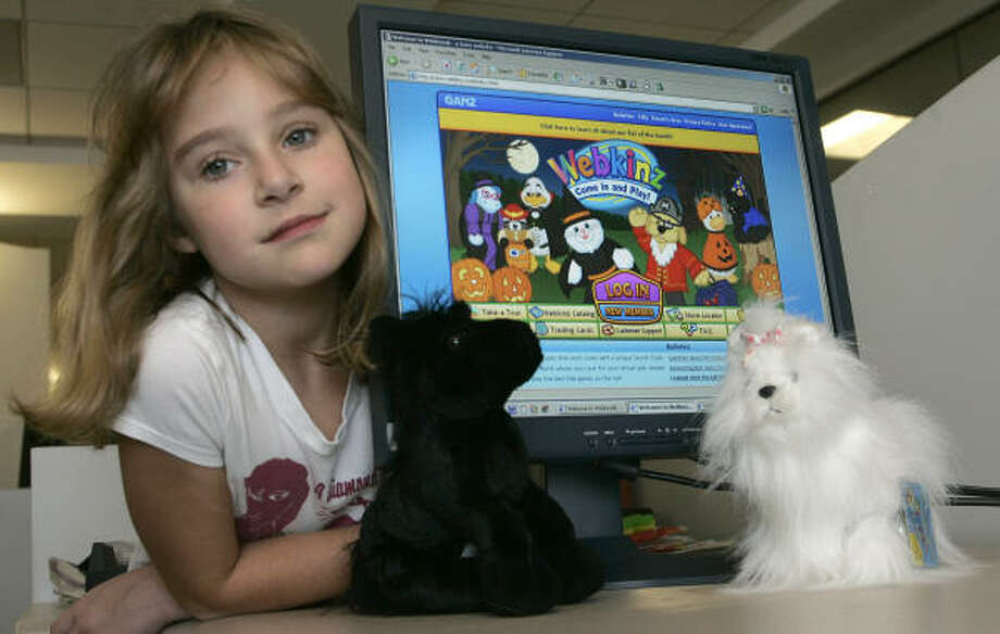 Ashling Cannon, 7, poses Oct. 29 next to a computer screen displaying the Webkinz Web site and her Webkinz cuddly toys in Washington.  Wal-Mart has a limited-time deal to sell Webkinz plush toys during the holiday season, hoping it will help during a difficult time for retailers. Photo: NICHOLAS KAMM, AFP/Getty Images