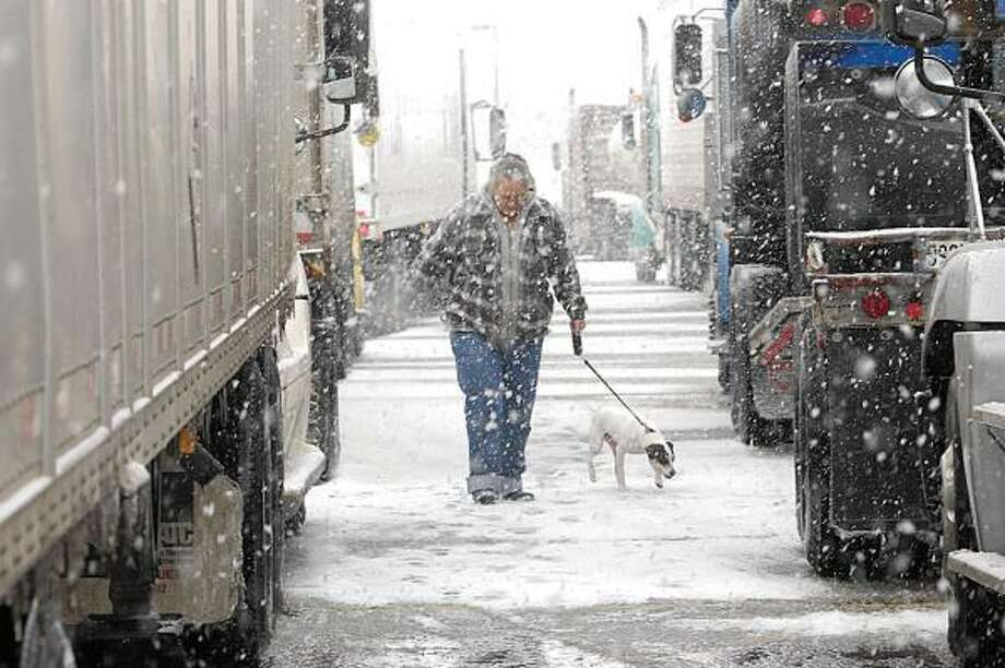 RaeDeane Brooks of El Dorado Springs, Mo., walks her dog Buddy among the stopped trucks Tuesday after authorities closed Interstate 10 during a snowstorm in Kerrville. Photo: John Schmid, Kerrville Daily Times