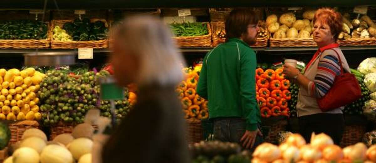 Customers peruse more than 160 varieties of fruits and vegetables at the Whole Foods Market at West Alabama and Kirby. The Austin-based company said it reached a deal to buy Boulder, Colo.-based Wild Oats Markets.