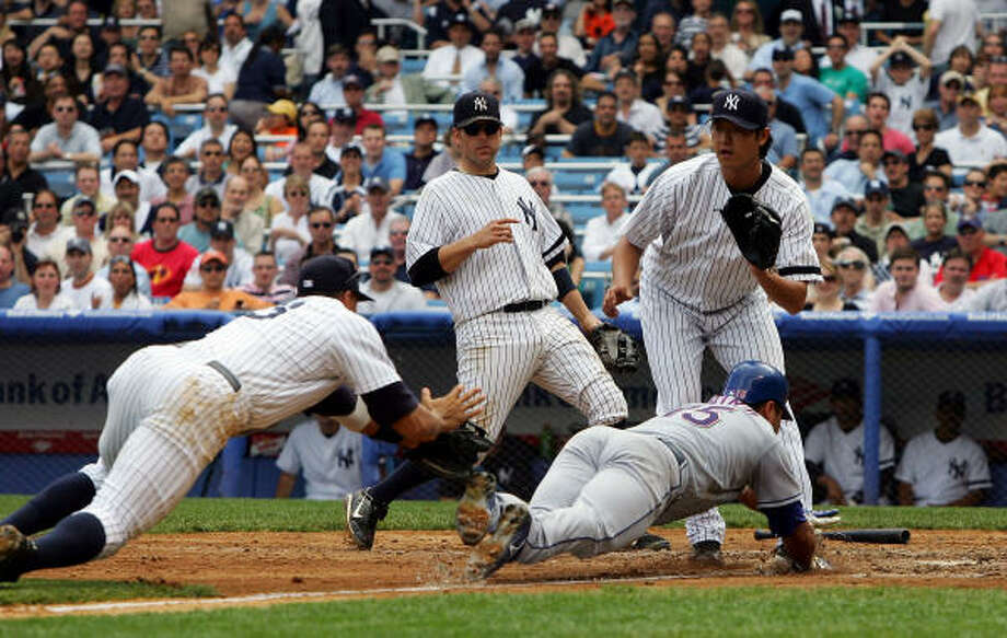 Beating Yankees third baseman Alex Rodriguez (left) to home plate, covered by pitcher Chien-Ming Wang, the Rangers' Gerald Laird (15) dives safely to put Texas up 2-1 in the fifth inning. Photo: Jim McIsaac, Getty Images