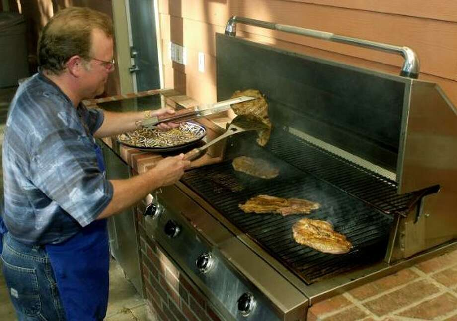 Ted Liggett cooks steaks on his infrared grill at his Lubbock home. The grill heats to temperatures higher than normal backyard grills and quickly handles meat, fish and other foods. Photo: JOE DON BUCKNER, ASSOCIATED PRESS FILE