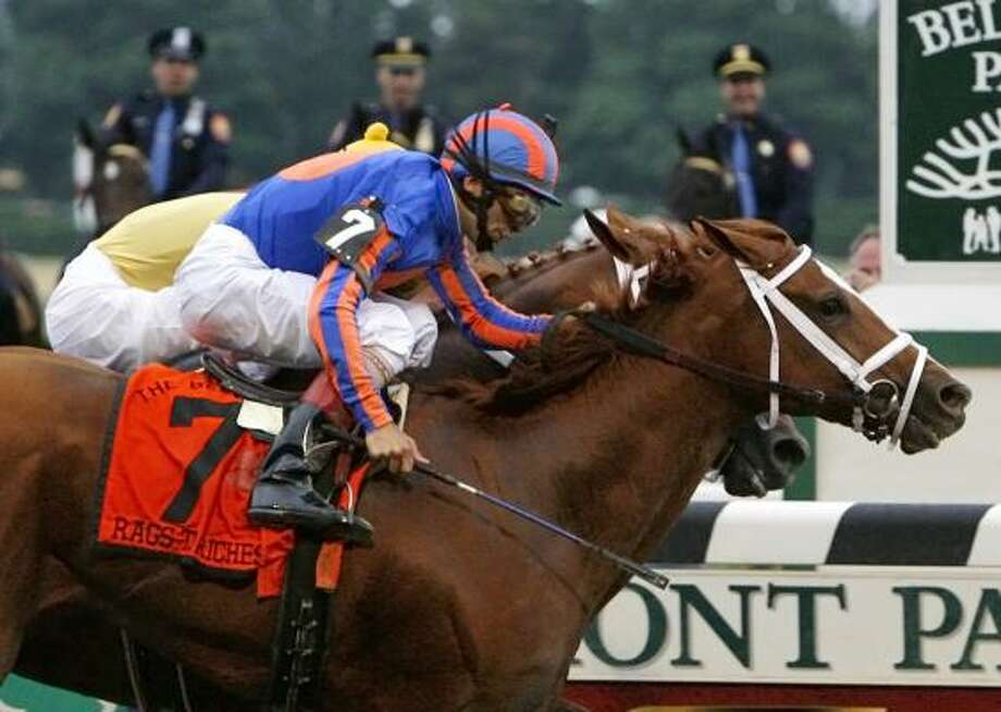 Rags to Riches (7), ridden by John R. Velazquez, crosses the finish line just ahead of Curlin to win Saturday's Belmont Stakes and become the first filly to do so since Tanya in 1905. Photo: Jason DeCrow, AP
