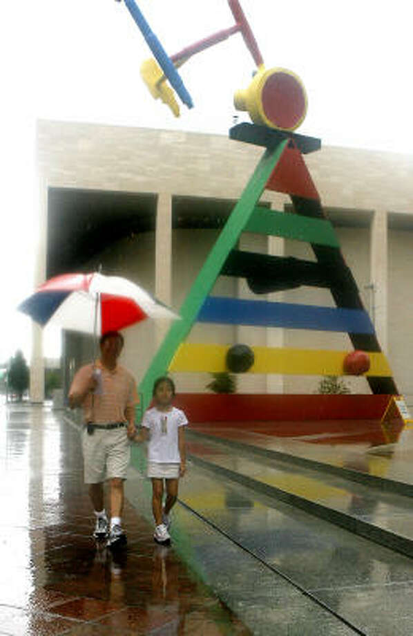 Steven Shu and his daughter, Jessica Shu, 8, both from Houston, walk past the Miro sculpture, which is in front of the Chase Tower. They didn't let the wet weather cut short their sight-seeing excursion in downtown Houston. Photo: Steve Campbell, Chronicle