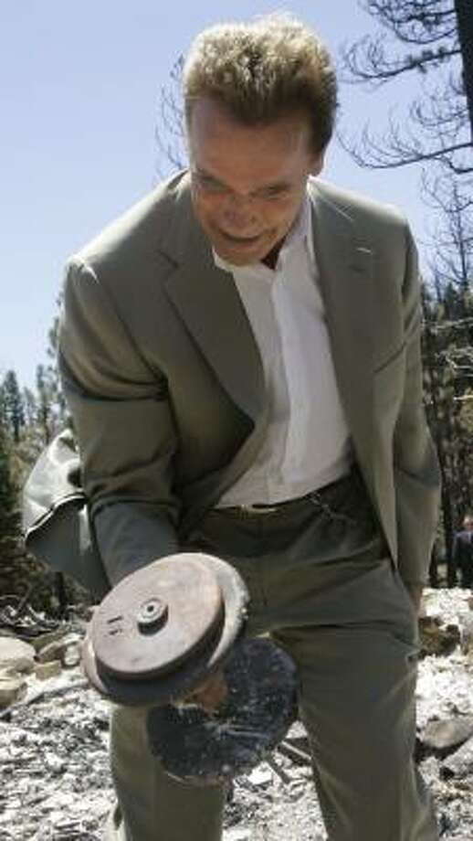 California Gov. Arnold Schwarzenegger on Wednesday picks up a dumbbell that was found in a house razed by wildfire. Photo: JEFF CHIU, AFP/GETTY IMAGES