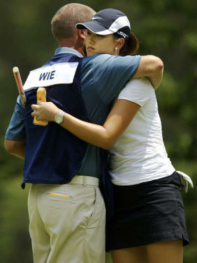 After her first-round 82, Michelle Wie (right) was in need of a hug. Caddie David Clark obliged on the 18th green. Photo: Jonathan Ernst, Getty Images