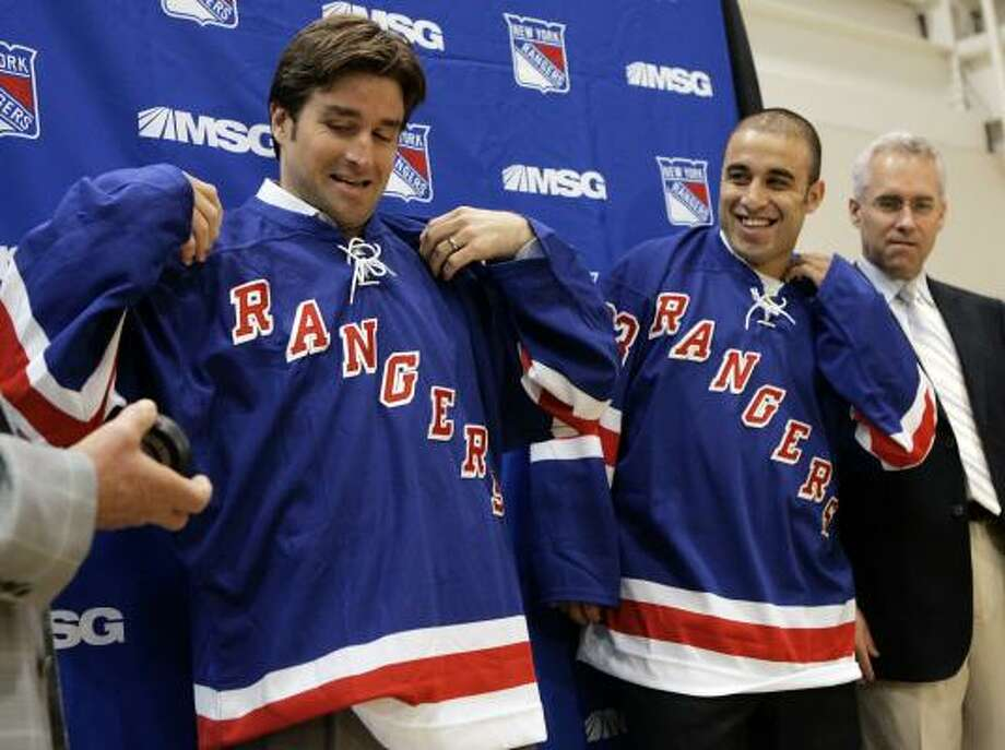 Newly-signed New York Rangers centers Chris Drury and Scott Gomez pull on their new sweaters as head hockey coach Tom Renney, right, looks on at the Rangers' training facility in Greenburgh, N.Y. Photo: Jeff Zelevansky, AP