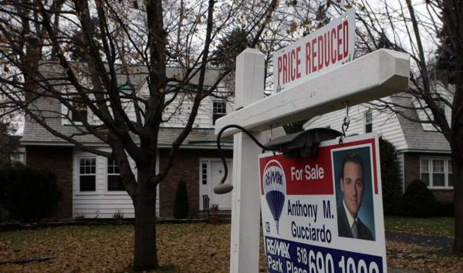 A homeowner tries to attract buyers with a sign offering a reduced price in Albany, N.Y. Home prices dropped 4.5 percent nationally in the third quarter. Photo: MIKE GROLL, ASSOCIATED PRESS