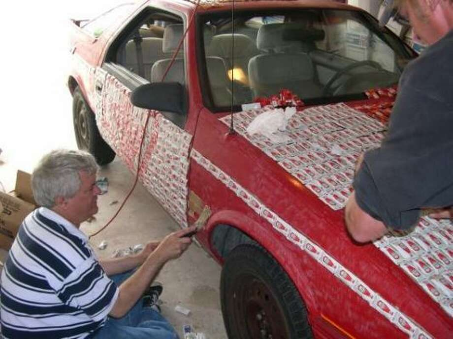 David Blacklock, left, pastes Heinz ketchup packages to Condiment Car 2. It took Blacklock and his friends Glen Lindquist, Steve Markham and Jack Markham about 30 hours to use carpenter's glue to stick about 4,000 packets of sauce on the car. Photo: Steven Markham, Contributed Photo