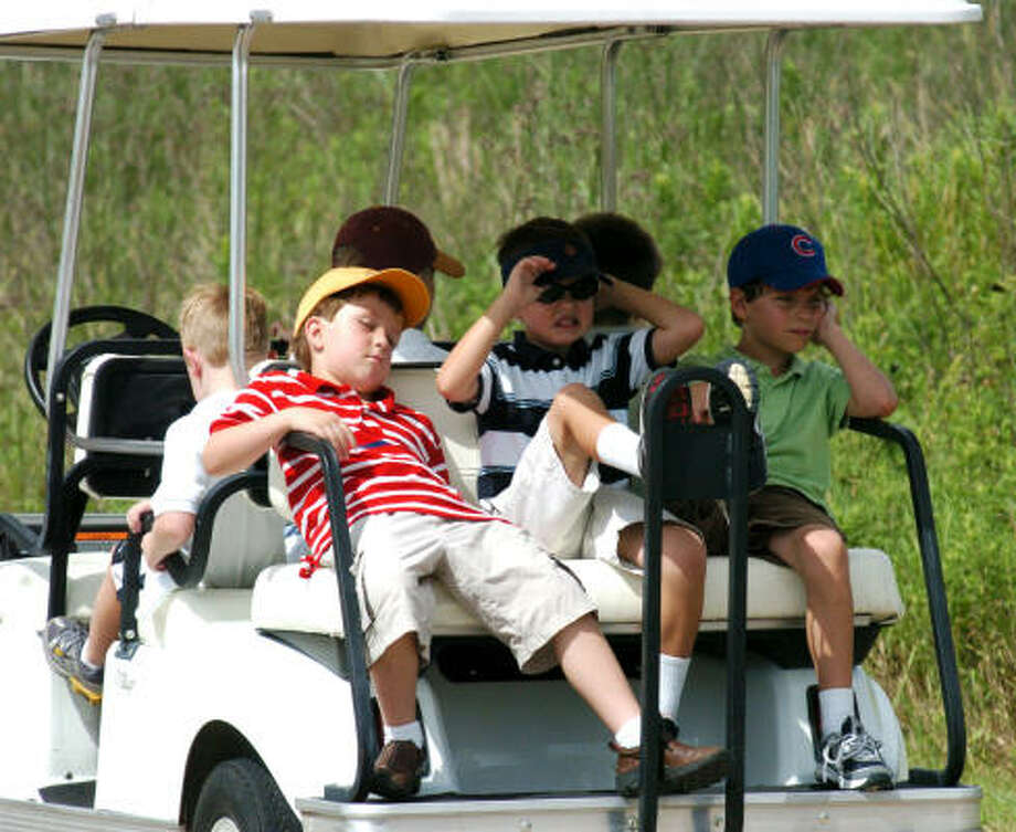 The back of a golf cart makes a good place to rest for, from left, Ryan Yates, Matthew Posoli and Michael Revis during Junior Golf Camp at Wildcat Golf Club. Photo: Kirk Sides, For The Chronicle