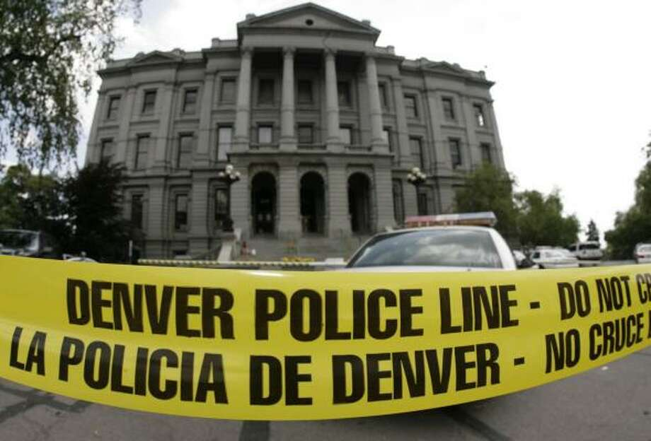 Police tape blocks the steps to Colorado's Capitol building Monday after police shot and killed a gunman who threatened the governor. The dead man's name and motive were not immediately known. Photo: DAVID ZALUBOWSKI, AP