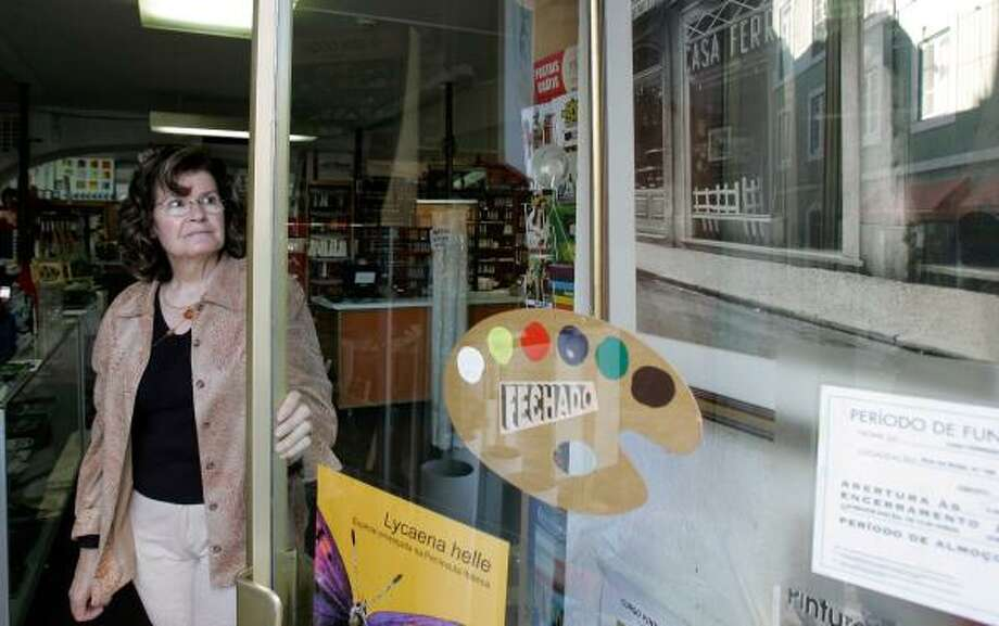 Jeronima Ferreira, manager of Casa Ferreira, a fine arts supply store in Lisbon, looks at a photograph of the company's now-closed second store, a metaphor for Portugal's tough economic times. Photo: ARMANDO FRANCA, ASSOCIATED PRESS