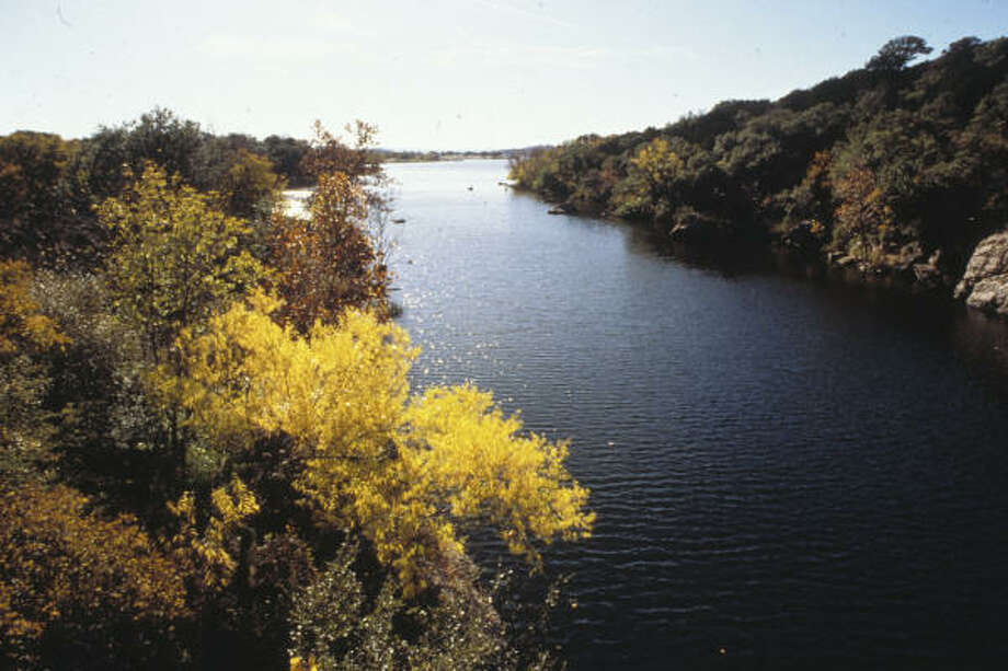 The banks of Inks Lake are covered with trees and dotted with rock outcroppings of pink gneiss. Photo: Texas Parks And Wildlife