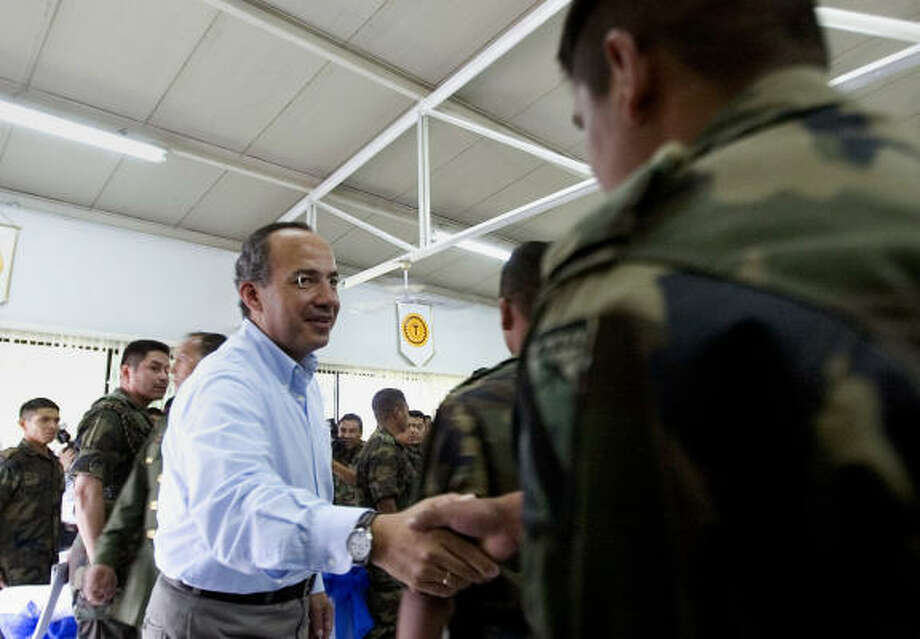 Mexican President Felipe Calderon greets a soldier at the base of the 43th Military zone in Apatzingan, Mexico, on Jan. 3. Photo: Guillermo Arias, ASSOCIATED PRESS
