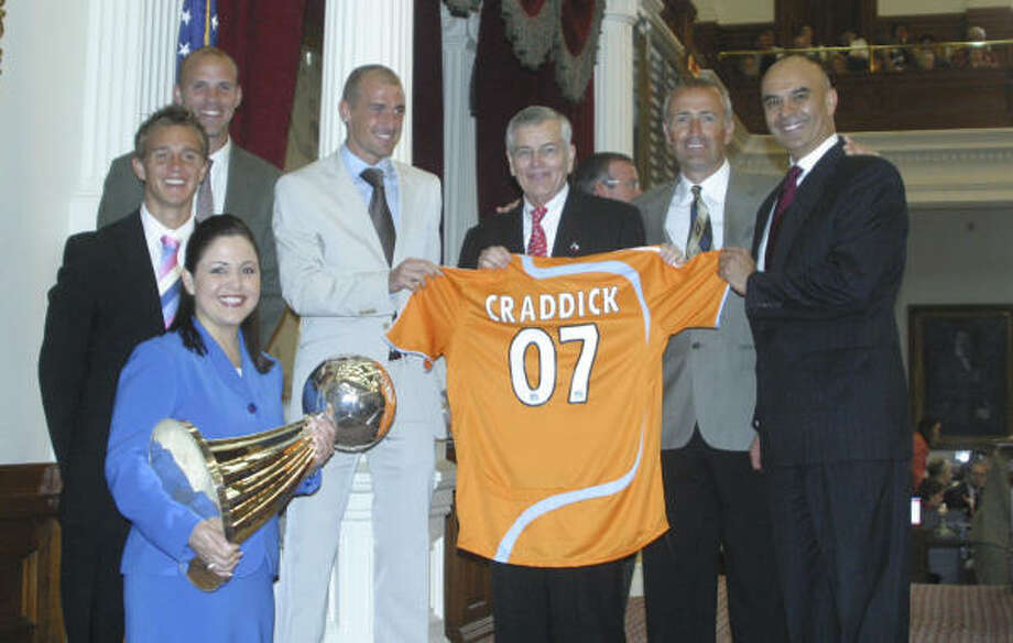 Dynamo players (from left) Stuart Holden, Craig Waibel and Paul Dalglish join State Rep. Ana Hernandez (bottom) and Rick Noriega (right), Speaker of the House Tom Craddick (center) and coach Dominic Kinnear at a congratulary ceremony at the State Capitol on Wednesday. Photo: Photo Courtesy Of Houston Dynamo
