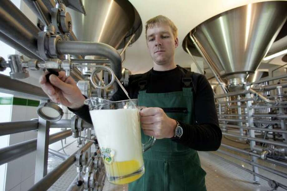 Brewer Michael Riesch takes a sample of light beer from a storage tank at the Ayinger brewery in Aying, southern Germany. The German government's subsidies for barley farmers to plant crops to produce biofuels is driving up the price of a key ingredient in beer. Photo: DIETHER ENDLICHER, ASSOCIATED PRESS