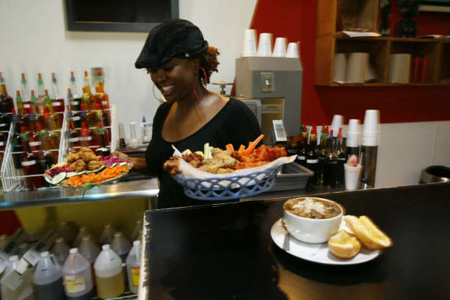 Lakesha Reed, 29, who has a marketing degree from the University of Houston, opened Beaucoup Wings and Wings near the school last year. But Reed intends to return to New Orleans eventually. ``Houston's cool; it's OK. But it's not the same feel that you get at home,'' she said. Photo: Melissa Phillip, Chronicle