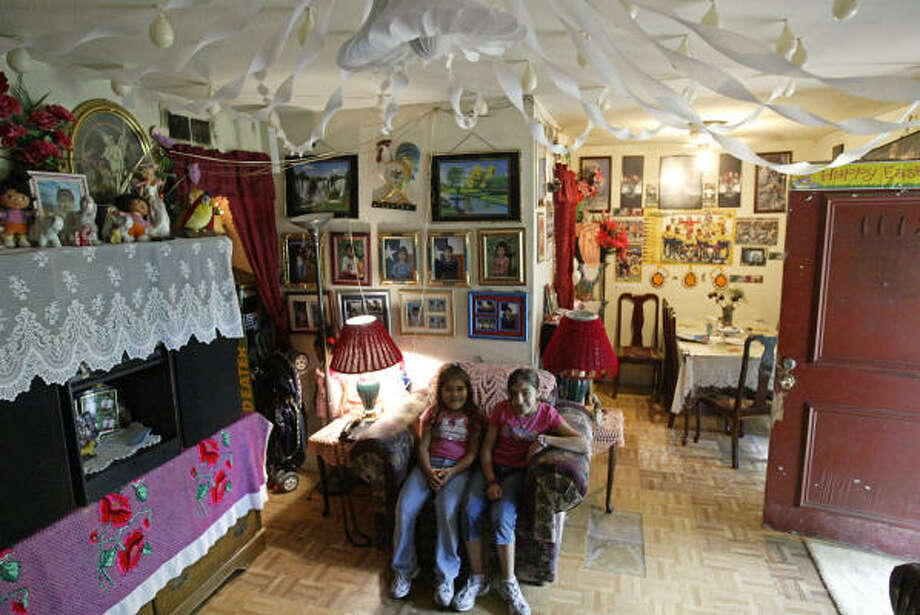 Araceli, 10, right, sits beside her sister Esmeralda, 9, left, inside their living room at Le Promenade Apartments. Photo: Jessica Kourkounis, For The Chronicle