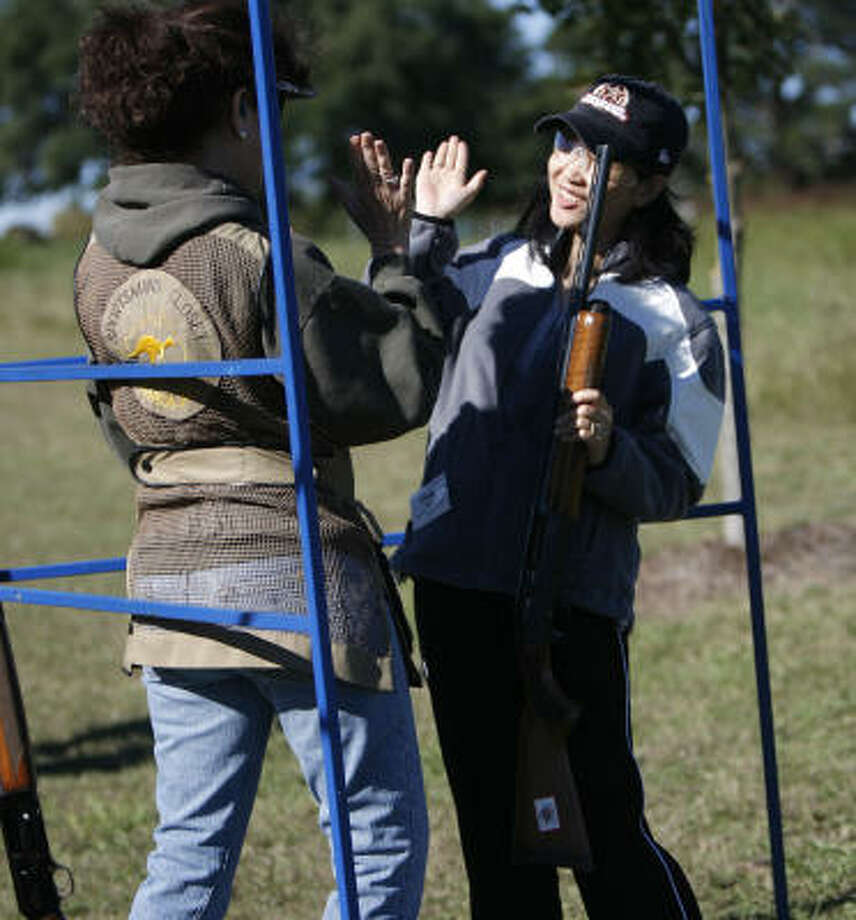 Shooting instructor Martie Holt, left, and Cindy Wang high-five each other after Wang broke her first clay target during a Texas Parks and Wildlife Department outdoors workshop devoted to women. Photo: KAREN WARREN, Houston Chronicle