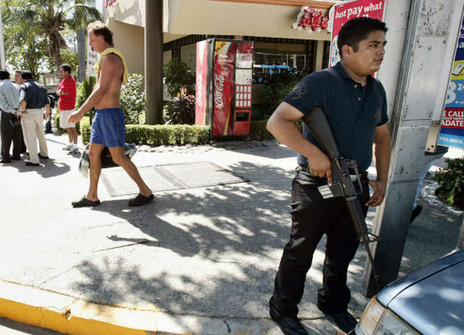 Tourists pass an armed policeman after a man was shot on the main avenue in the resort city of Acapulco, Mexico, on Feb. 8. Violence continues to plague this city, where gunmen dressed as soldiers staged and videotaped simultaneous assaults on two offices of the state attorney general, killing at least seven people. Photo: Gregory Bull, AP