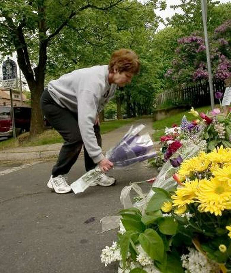 Janna Schultz lays flowers at a makeshift memorial set up for slain Moscow police officer Lee Newbill at the intersection of Van Buren Street and Third Street in Moscow, Idaho, Sunday. Photo: Dean Hare, AP