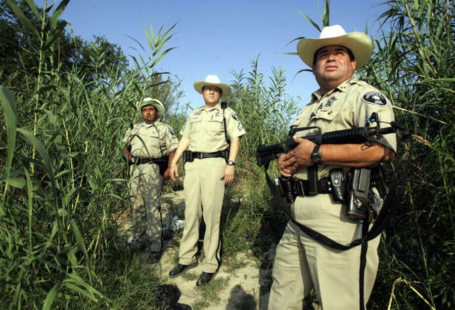 Webb County Sheriff Officers Captain Manuel Gomez Jr, right, Sargent Ricardo Garcia, center, and Deputy JJ Cabazos inspect a section of the Rio Grande. Photo: HECTOR MATA, AFP/Getty Images