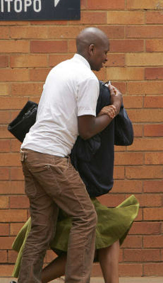 Former dormitory matron Virginia Tiny Makgoba is whisked out of Sebokeng Magistrate Court south of Johannesburg. Makgoba is accused of abuse, indecent assault, crimen injuria and soliciting underage girls to perform indecent acts. She was was granted bail of about $450 and her case was postponed until Dec. 13. Photo: ALEXANDER JOE, AFP/Getty Images