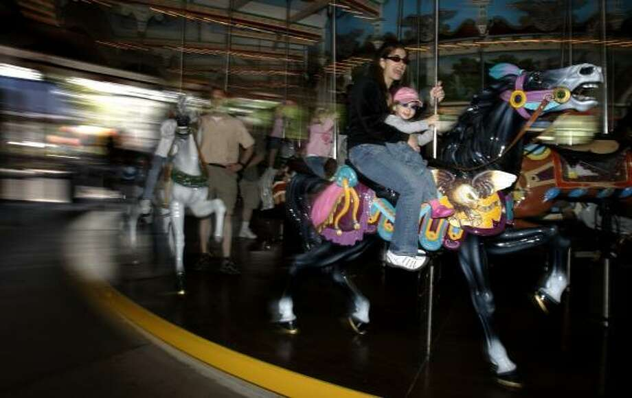 Danille Rotoroti and daughter Julia, 2, ride the carousel at Hershey Co.'s theme park in Pennsylvania in May. The charitable trust that controls the company wants to overhaul its board. Photo: CAROLYN KASTER, ASSOCIATED PRESS FILE