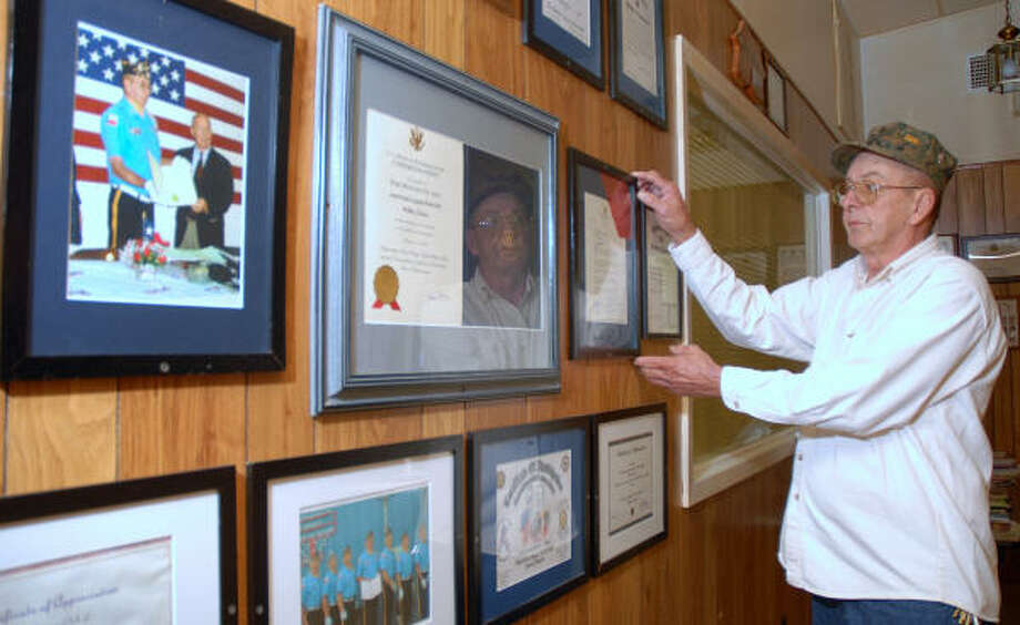 Veteran Bob Baker hangs another award on the Post's Honor Guard wall. He is a member of the American Legion Post 618, Willis, Honor Guard. He plays taps and participates in veterans' funerals and other community events. Photo: David Hopper, For The Chronicle