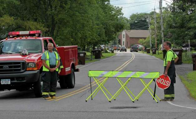 Voorheesville firefighters Don Houck, left, and John Hensel block off traffic Wednesday at the intersection of 85A and Mountainview Street in Voorheesville. Three women were killed wheny they were struck by a runaway SUV outside of St. Matthew's Church. (Erin Colligan / Special to the Times Union)