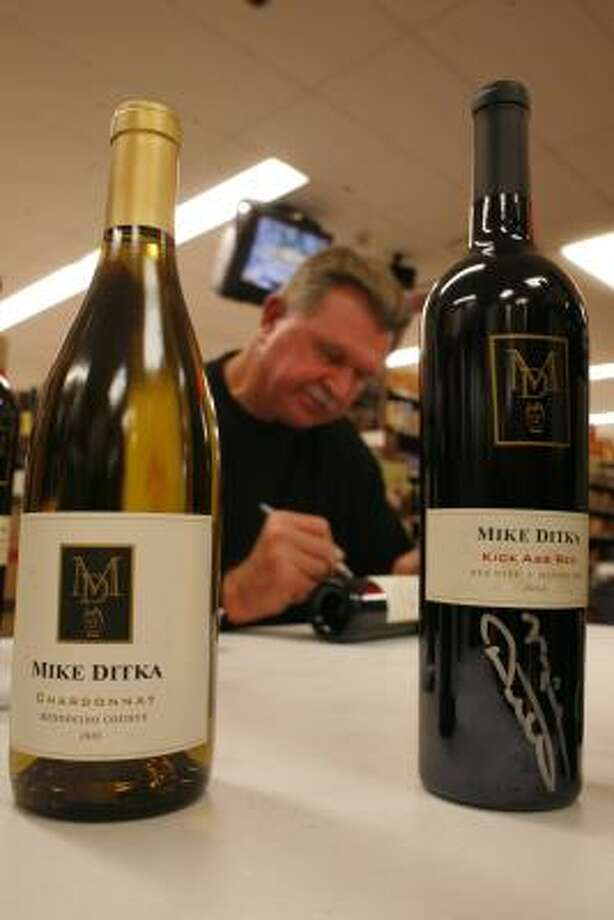 Mike Ditka autographs wine bottles during a recent visit to Spec's. Photo: Steve Ueckert, Chronicle