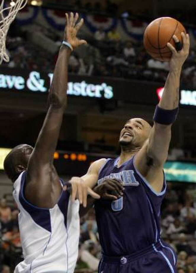 Utah's Carlos Boozer (5) goes strong to the basket against Dallas' DeSagana Diop (7) during the first quarter Friday night. Photo: TIM SHARP, ASSOCIATED PRESS