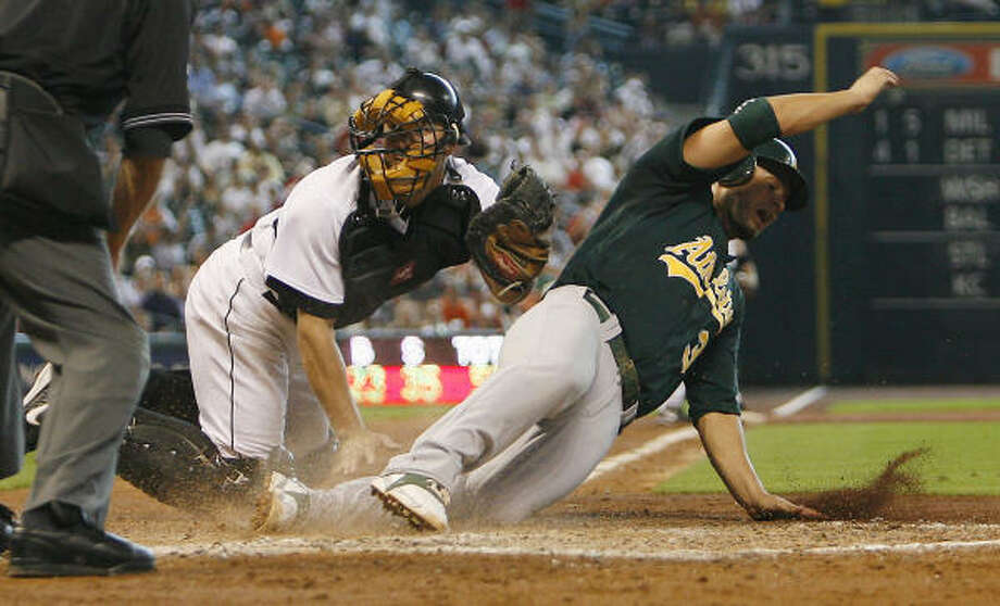 Eric Munson tags out A's third baseman Eric Chavez after taking a throw from Carlos Lee in the third inning. Photo: Bob Levey, For The Chronicle