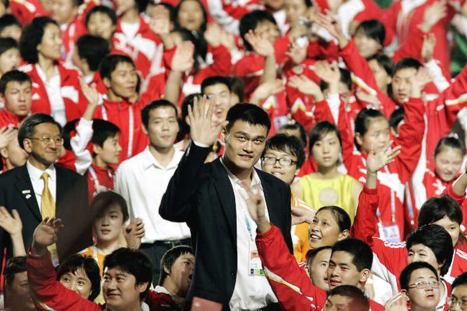 Rockets' star Yao Ming, center in black suit, was happy he stayed a few extra days in Shanghai, China, to attend the Special Olympics Global Games and agreed with the Rockets' decision to fine him for his tardiness. Photo: EUGENE HOSHIKO, AP