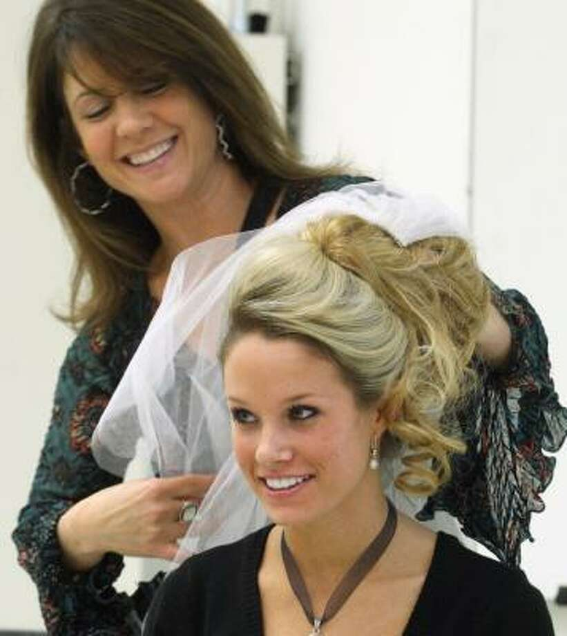 Guest vendor Giselle demonstrates a wedding hairstyle on Brittney Tobin, 19, a student in a class on wedding planning at George Mason University in Fairfax, Va. It is apparently the first such class in the country at a four-year college. Photo: RICHARD A. LIPSKI, WASHINGTON POST
