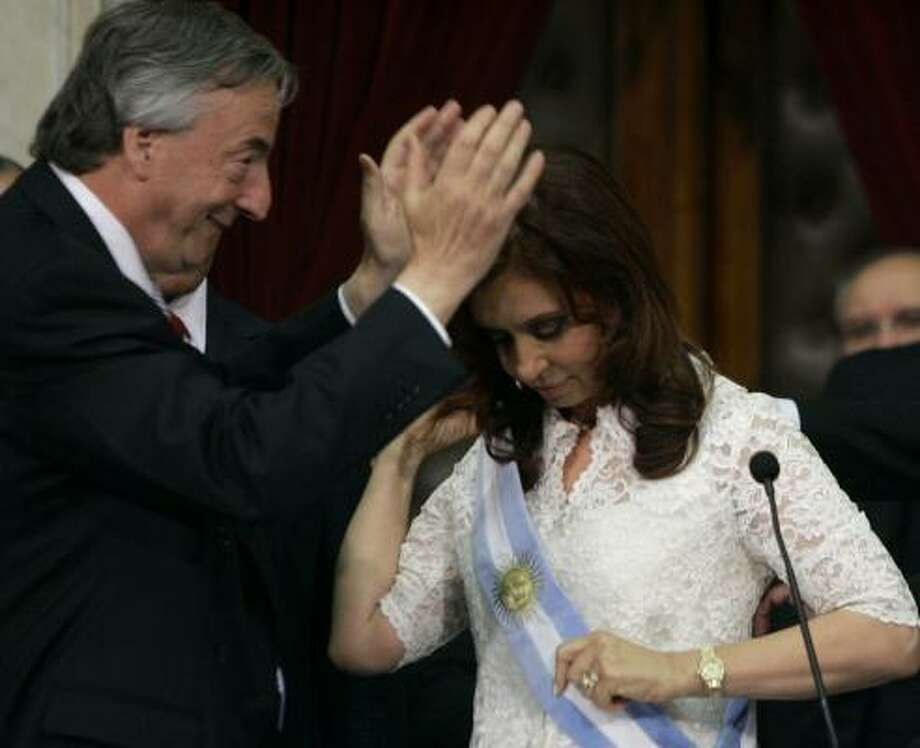 Argentina's departing president, Nestor Kirchner, gestures after handing the presidential sash to his wife and new president, Cristina Fernandez, in Buenos Aires on Monday. Photo: JORGE SAENZ, ASSOCIATED PRESS