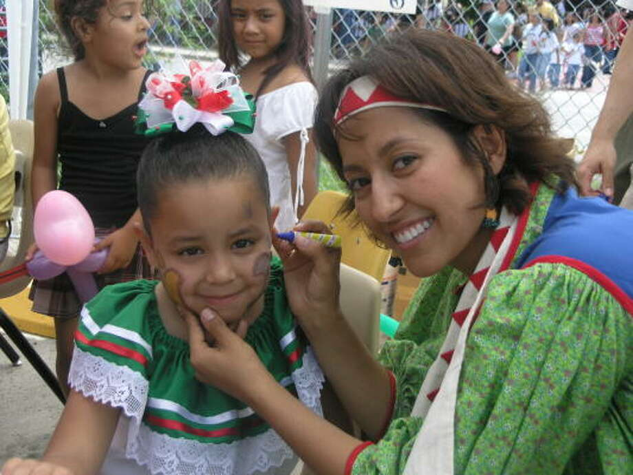 Maria Loza, 6, was among those who got her face painted by Scroggins Elementary School kindergarten teacher Alejandra Nevarez as more than 600 residents came out to support a fundraising effort on behalf of Miguel Moctezuma. The Reagan High School senior was set to graduate as school's valedictorian, but collapsed March 3 as a result of a brain aneurysm. Photo:  Fannie Williams, For The Chronicle