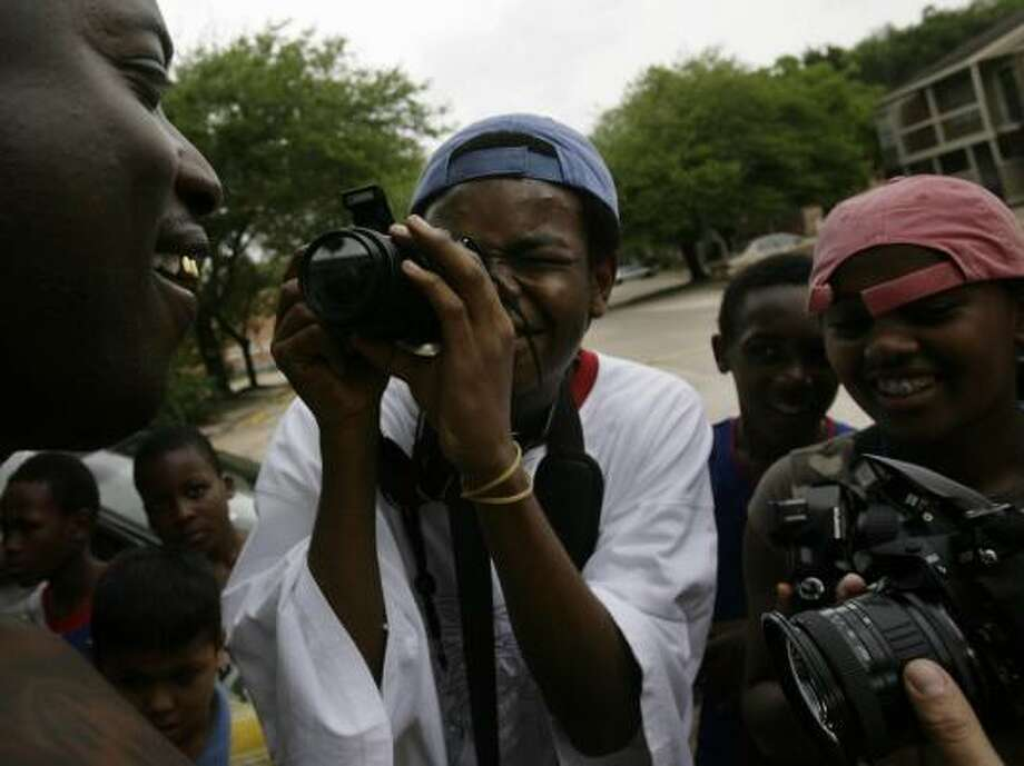 Lewis Kabongo, center, of the Congo, and Salem Gebrase Lassie, right, of Ethiopia, were among 20 youths who took photographs of residents of the Glendale Park apartment complex during last month's National Geographic Photo Camp, which was part of Houston Grand Opera's Song of Houston project. Their photographs were played as a slide show during the recent World Refugee Day activities. Photo: MAYRA BELTRAN, HOUSTON CHRONICLE