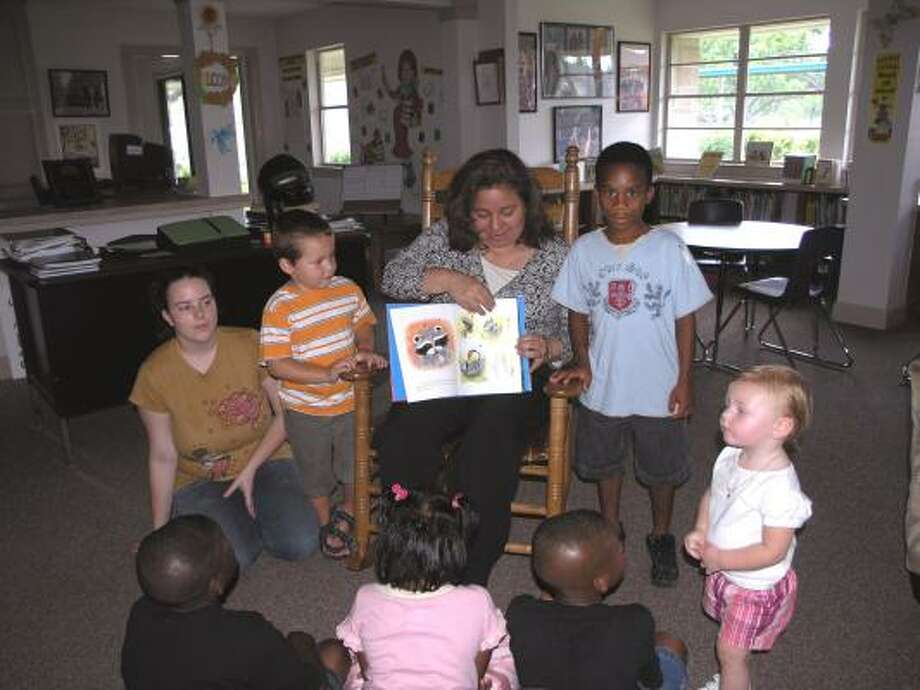 Volunteer Esmeralda Olvera of La Porte shares a story with Boys and Girls Harbor residents from left, Annie Lee, Caleb Johnson, Devonte Johnson, and infant Kaitlyn Ross. Photo:  Fannie Williams, For The Chronicle