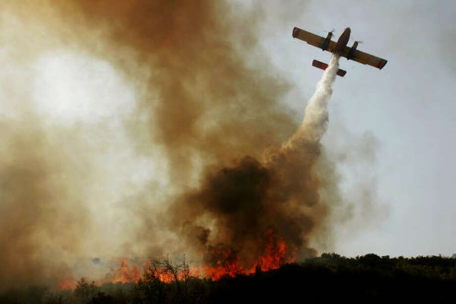 A firefighting plane drops water on a fire near Karytena village in Peloponnese on today. Photo: PETROS KARADJIAS, Associated Press