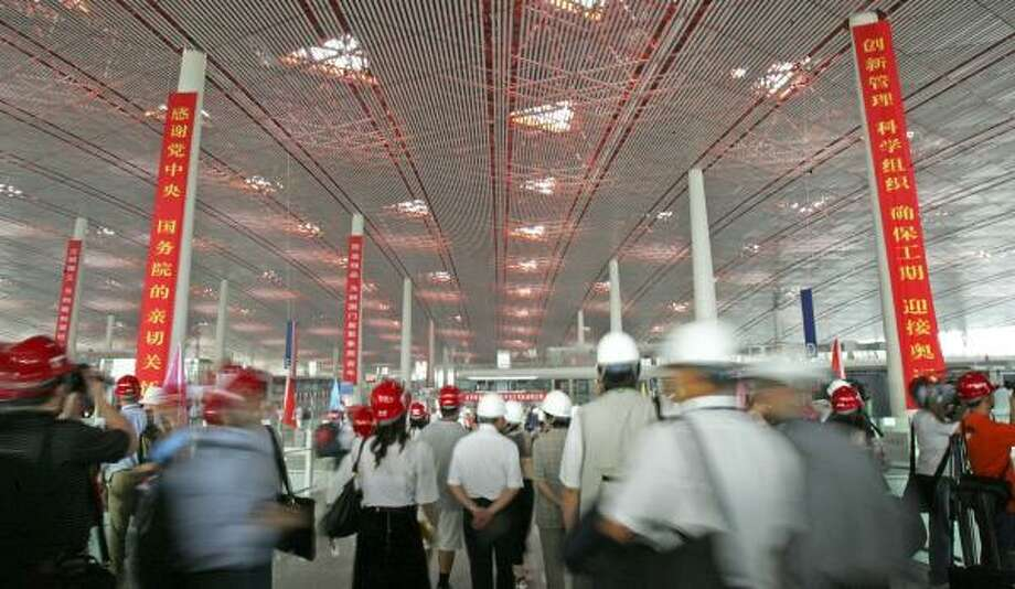 Members of the press wearing safety helmets enter Beijing's new terminal at Beijing Capital International Airport on Wednesday. Photo: WONG MAYE-E, ASSOCIATED PRESS