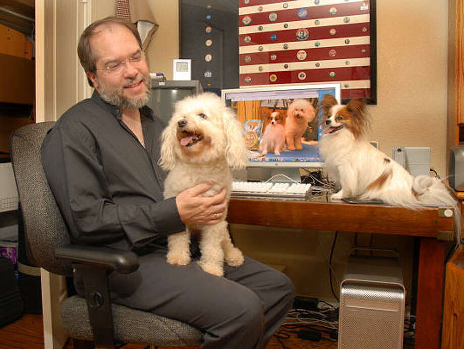 """Cochran's Crossing resident Frank Eakin holds Elka, as Rufus sits on the desk next to a computer image of the two dogs. Eakin wrote and produced the movie """"The Bracelet of Bordeaux,"""" featuring the dogs. Photo: David Hopper, For The Chronicle"""