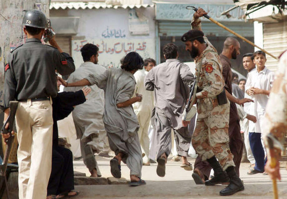 Pakistani paramilitary soldier beats protesters in Karachi, Pakistan, on Monday. A general strike paralyzed Karachi and closed businesses in other major Pakistani cities as discontent grew over President Gen. Pervez Musharraf's ouster of the chief justice and a weekend of violence that left 41 people dead. Photo: Mohammad Khalil, AP