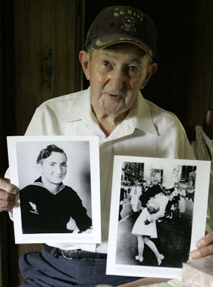 Glenn McDuffie holds a portrait of himself as a young man, left, and a copy of Alfred Eisenstaedt's iconic Life magazine shot of a sailor embracing a nurse. McDuffie says he is the sailor in the photo. Photo: PAT SULLIVAN, AP
